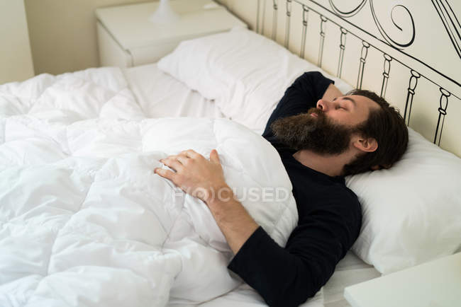 Bearded man lying in bed — Stock Photo
