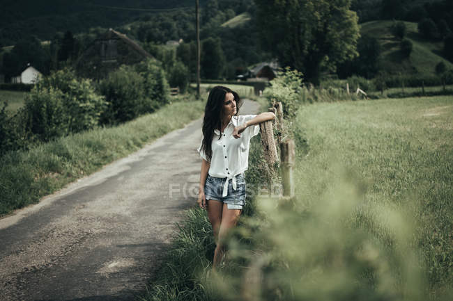 Pretty woman at rural fence — Stock Photo