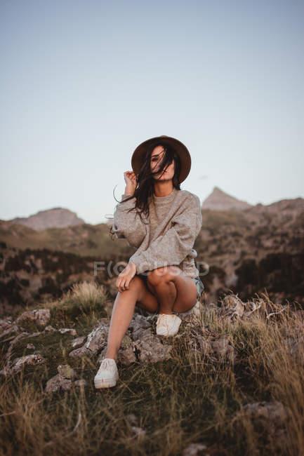 Femme dans une journée venteuse sur rocher — Photo de stock