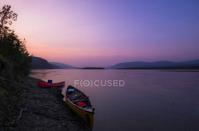 Kayaks on shore of lake in sunset — Stock Photo