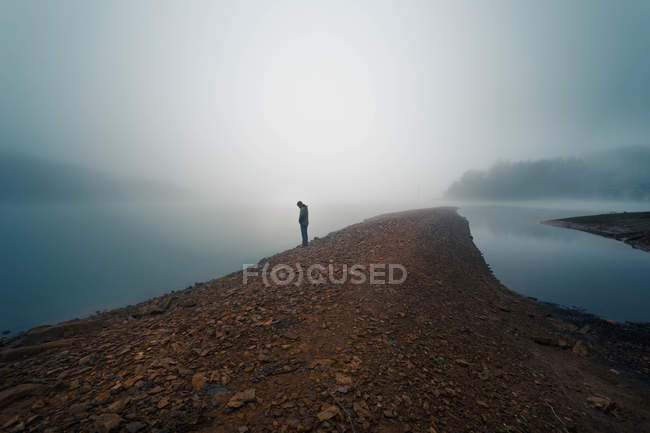 Anonymous person on misty shore — Stock Photo