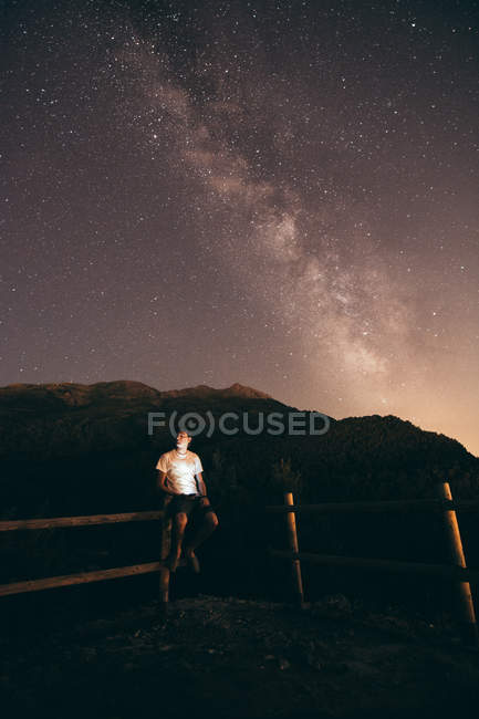 Man sitting on fence at night — Stock Photo