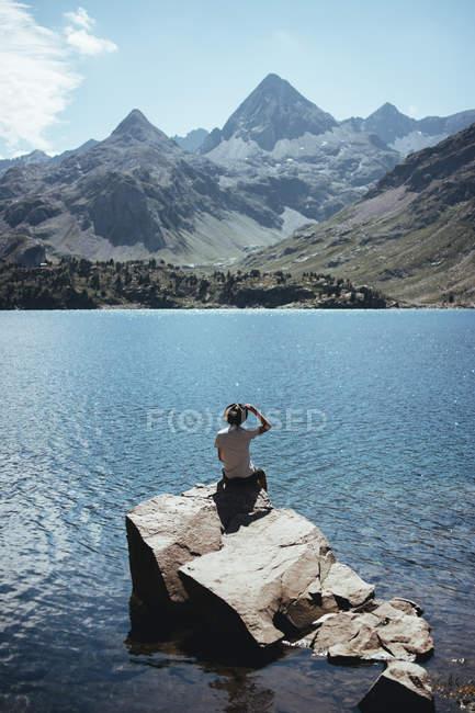 Homem na rocha, olhando para o lago — Fotografia de Stock