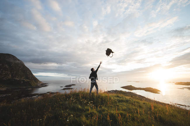 Man throwing backpack on landscape — Stock Photo