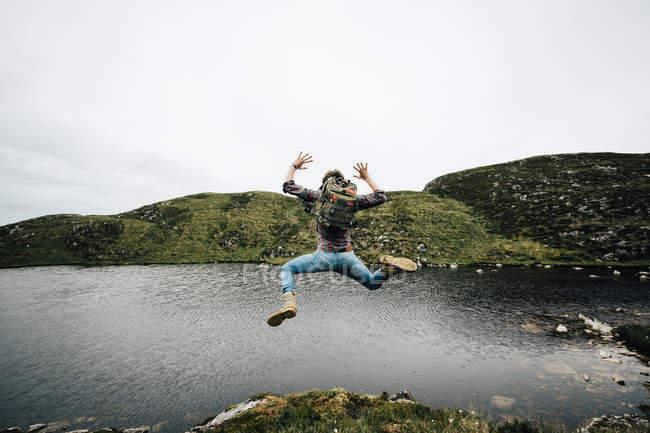 Backpacker springt über Landschaft — Stockfoto