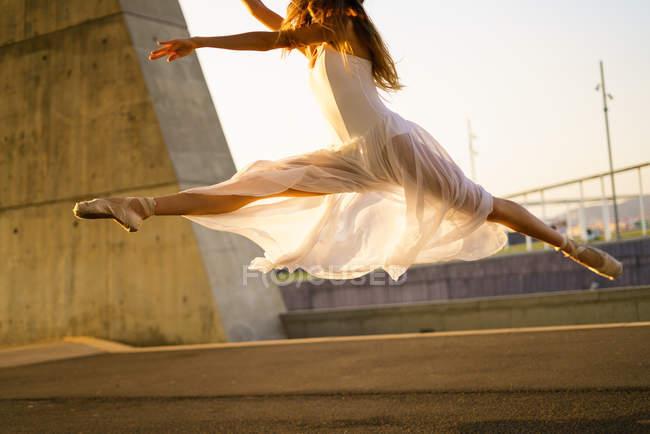 Crop ballerina jumping in midair at urban park — Stock Photo