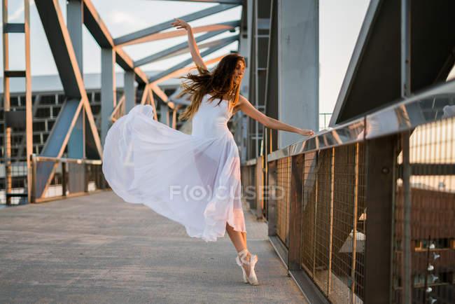Brunette ballerina in white dress posing on urban bridge in sunlight — Stock Photo