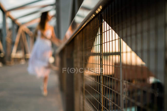Close up grid fence on background of blurred ballerina in sunlight — Stock Photo