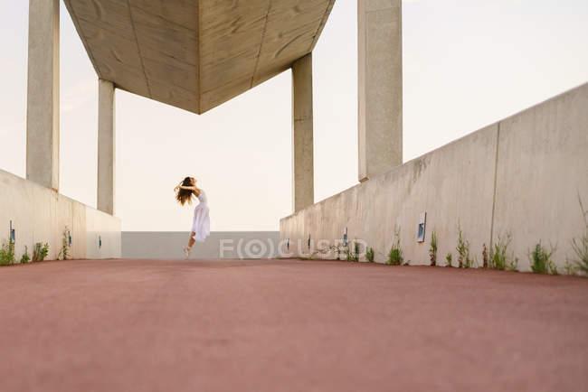 Поверхности уровня вид молодая брюнетка в белом платье, выполняя балета под строительство — стоковое фото