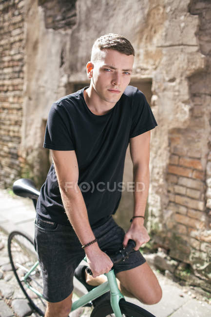 Хлопчик в чорному на велосипеді — стокове фото