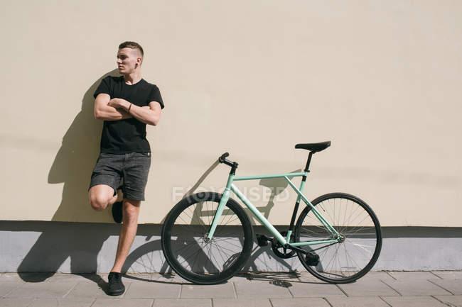 Boy leaning on wal beside bike — Stock Photo