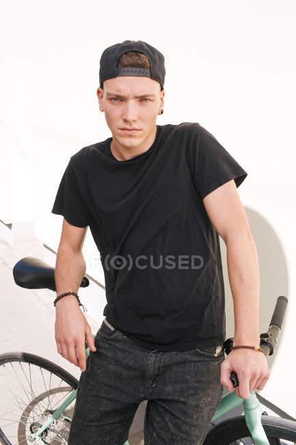 Хлопчик в Кап, сидячи на зелений велосипеда — стокове фото