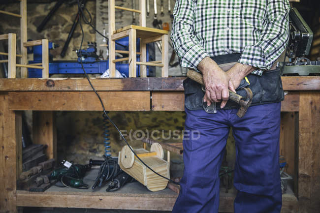 Midsection of man in checkered shirt standing with hammer in hand at workshop — Stock Photo
