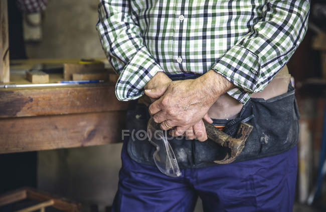 Midsection of man standing with hammer in hand at workshop — Stock Photo