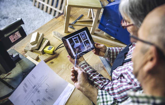 Over head view of senior couple comparing photos on tablet with blue print at workshop — Stock Photo