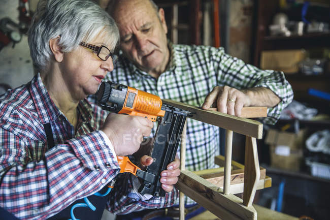 Side view of senior woman using fret saw at workshop — Stock Photo