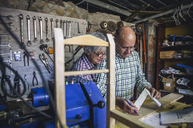 Senior couple working at workbench in carpenter workshop — Stock Photo