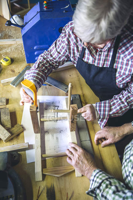 Senior woman gluing details of wooden chair at workshop — Stock Photo