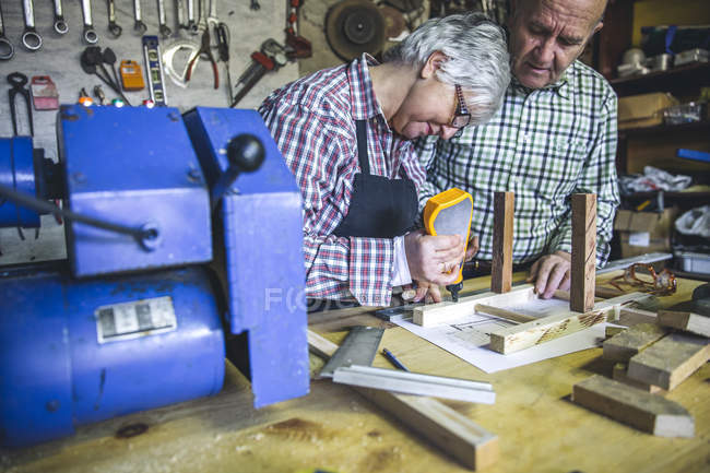Senior woman gluing details of wooden chair at workbench — Stock Photo