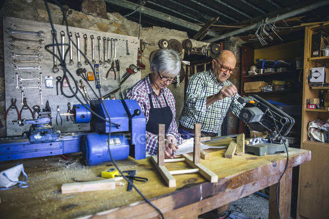 Senior couple working on workbench at carpenter workshop — Stock Photo