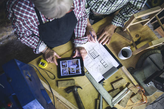 From above view of senior woman using tab at workbench — Stock Photo