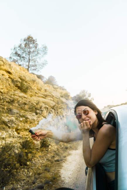 Girl posing in car with smoke bomb — Stock Photo