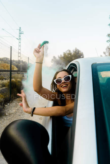 Girl posing with smoke bomb in car — side view, copy space - Stock