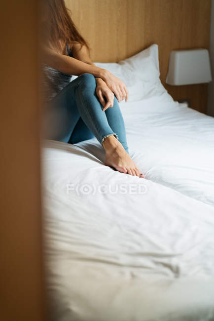 Crop female legs on bed at home — Stock Photo