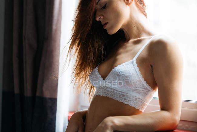 Young sensual girl in white lace bra standing near window and bending on sill. — Stock Photo