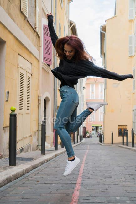 Femme portant des vêtements décontractés, sauter à cause de bonheur. — Photo de stock