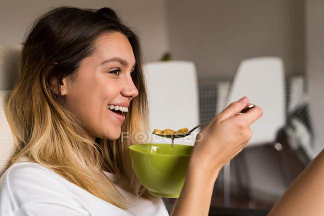 Веселая женщина ест хлопья — стоковое фото