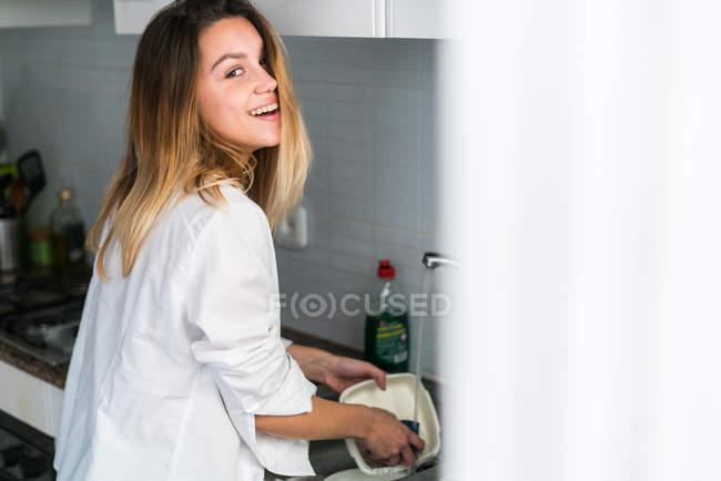 Femme gaie laver la vaisselle — Photo de stock