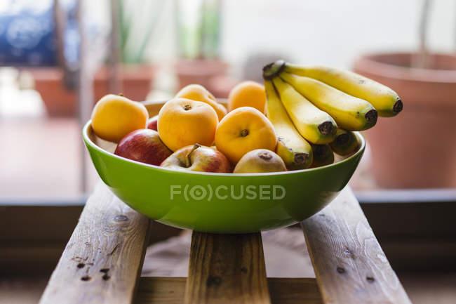 Свежие фрукты в миске на деревянной поверхности — стоковое фото