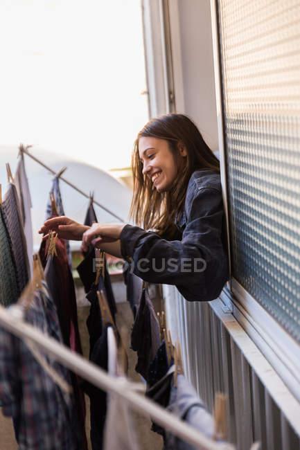 Donna sorridente che appende fuori servizio lavanderia — Foto stock