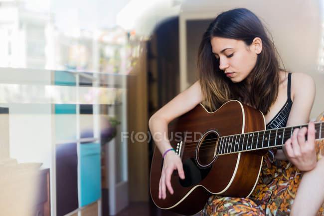 Молода дівчина з гітарою через вікно — стокове фото