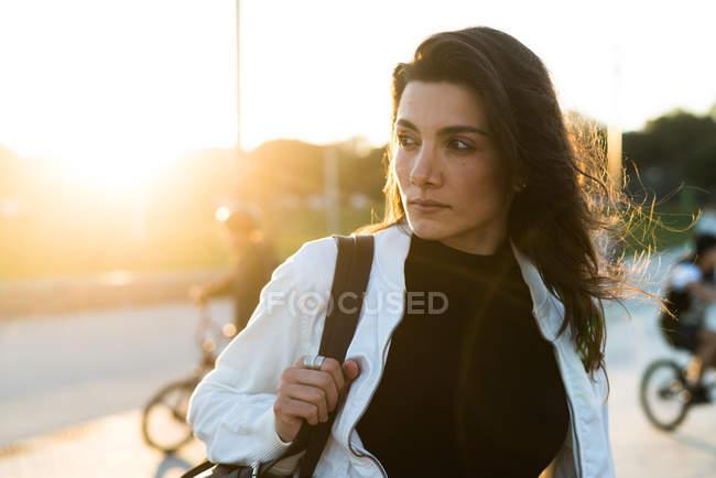 Стильний молода дівчина з рюкзака при сонячному світлі — стокове фото