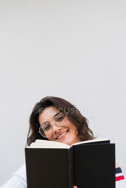 Souriant fille tenant livre — Photo de stock