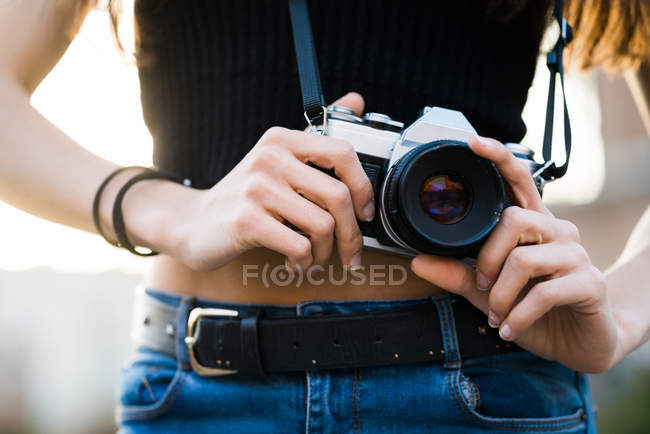 Hands of woman setting camera — Stock Photo