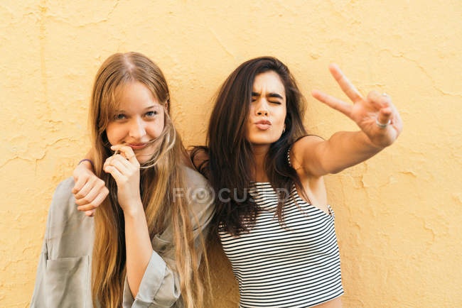 Teen girlfriends showing peace signs. — Stock Photo