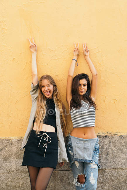 Teen girlfriends posing with arms up — Stock Photo