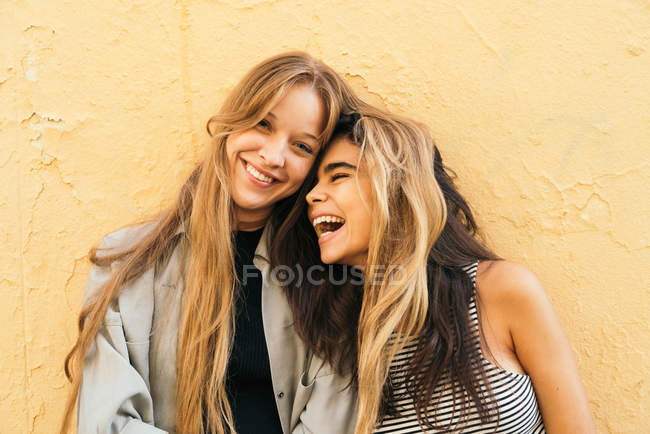 Laughing girlfriends on yellow — Stock Photo