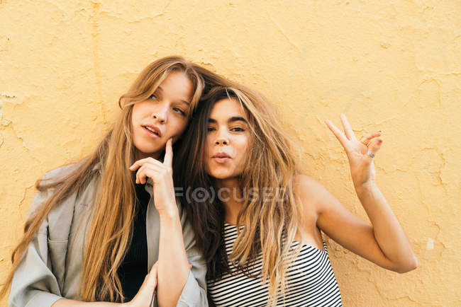 Teen girlfriends showing peace signs — Stock Photo