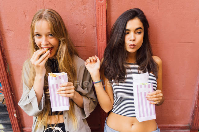 Pretty girls with popcorn paper bags — Stock Photo