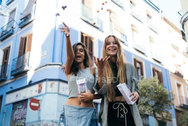 Smiling girls throwing popcorn at camera — Stock Photo