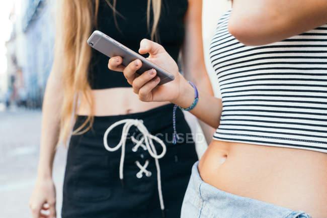 Duas meninas sexy irreconhecíveis usando smartphone — Fotografia de Stock