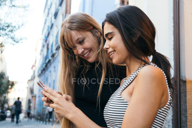 Two young girlfriends using smartphone — Stock Photo