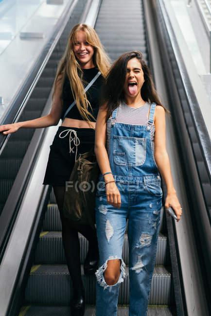 Радостное подругами весело на эскалаторе — стоковое фото
