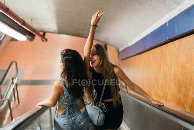 Радостное молодых девушек на эскалаторе — стоковое фото