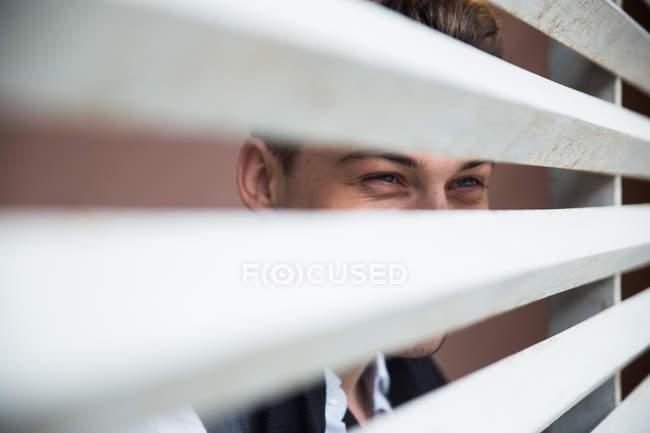 Schuss durch Jalousien eines jungen Mannes — Stockfoto