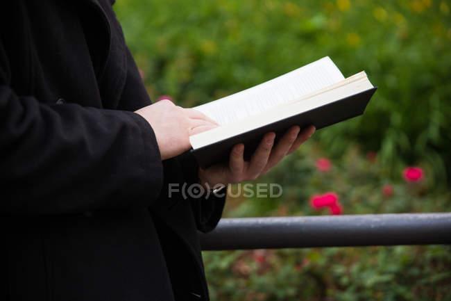 Mann Lesebuch außerhalb — Stockfoto
